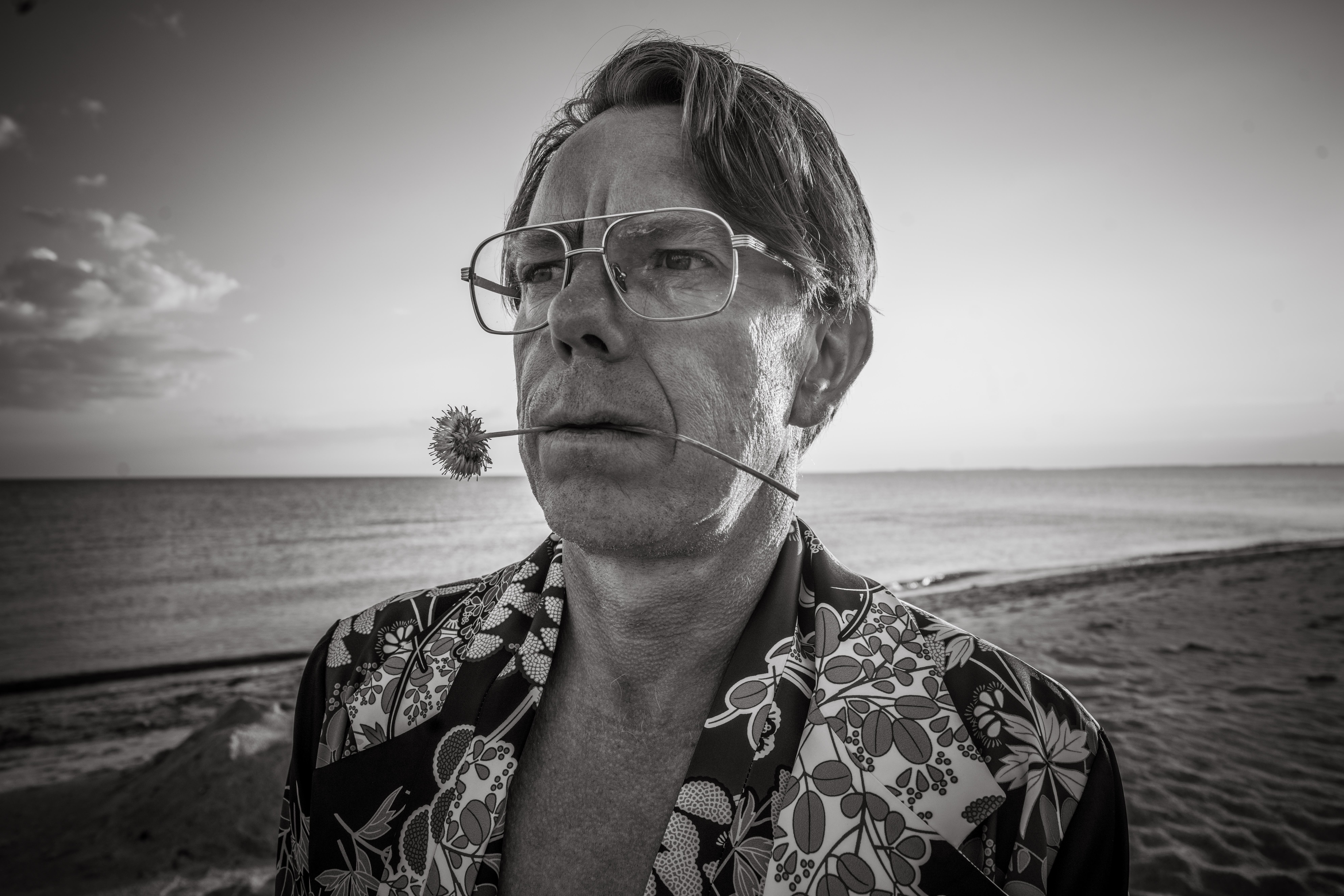 man in kimono on a beach with flower between lips