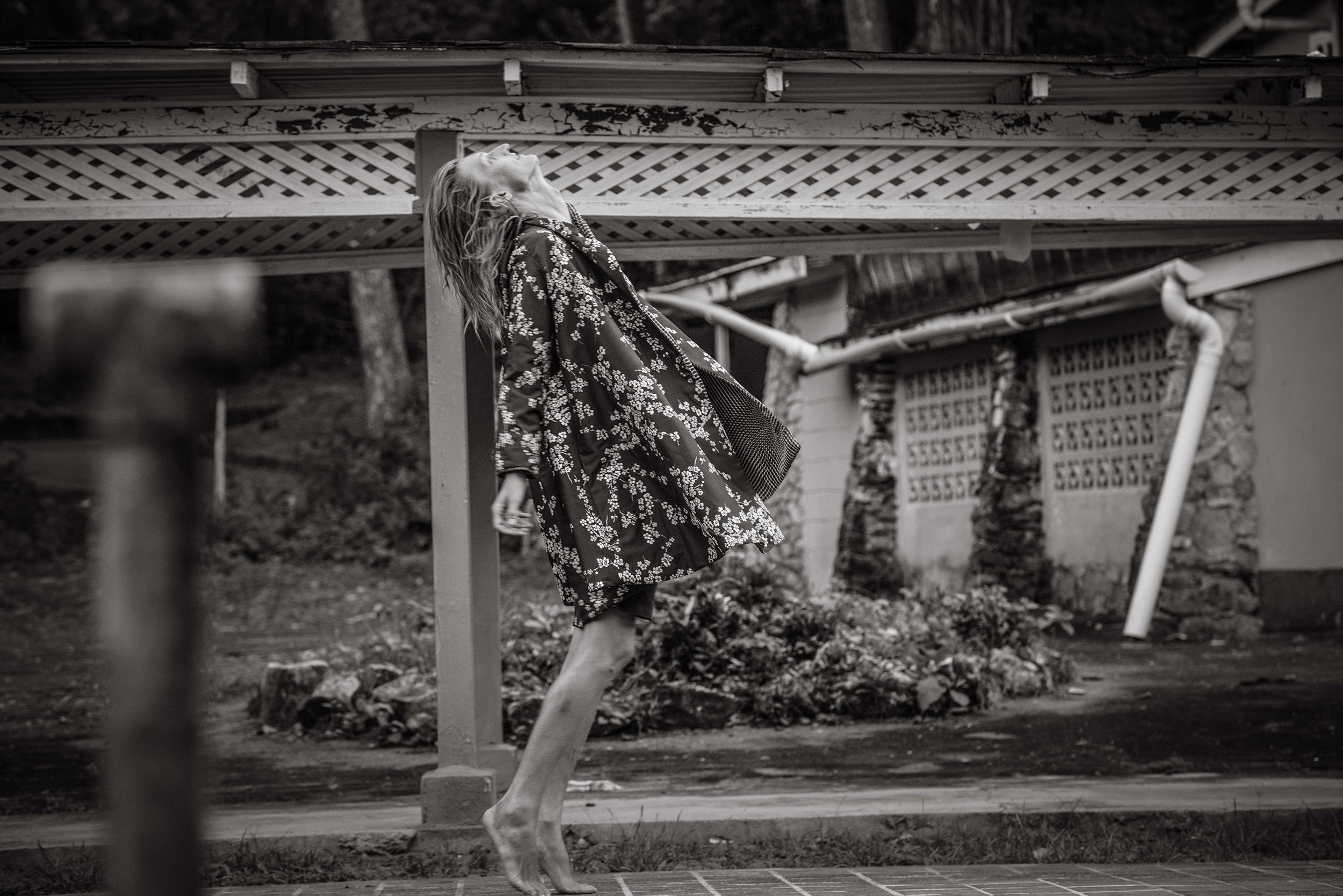 profile of backhanding model nik in front of abandoned hotel